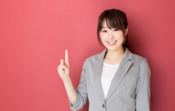 portrait of asian businesswoman pointing on red background
